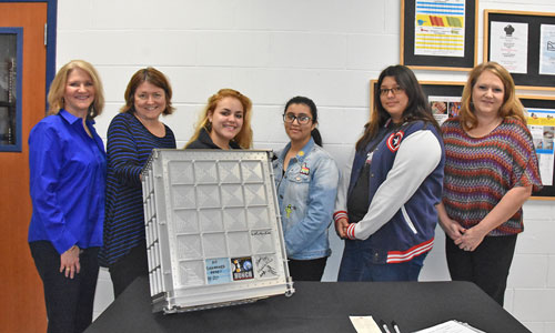 Chosen students hold up the signed stowage locker with Fashion Design teacher and NASA HUNCH manager.