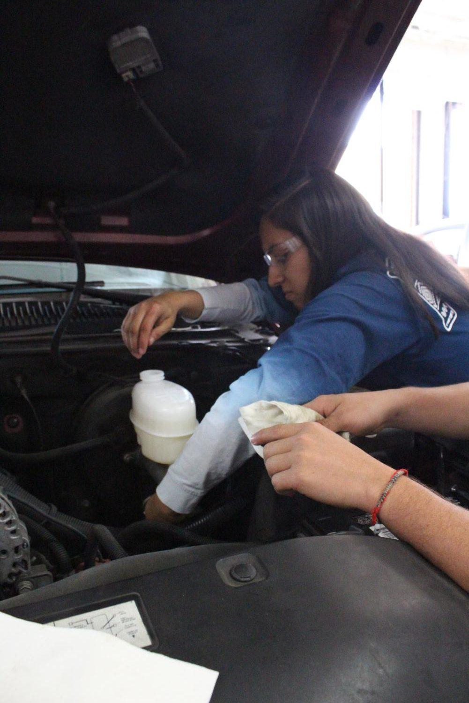 Senior Diana Hernandez works on a car's engine to improve her skills in auto mechanics.
